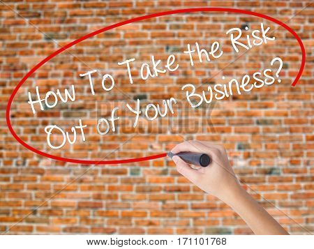 Woman Hand Writing How To Take The Risk Out Of Your Business? With Black Marker On Visual Screen