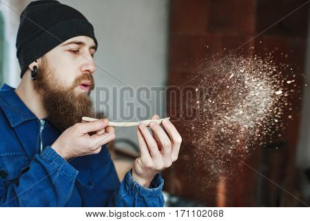 Man with a beard wearing blue jeans suit and black hat holding wooden spoon and blowing dust, woodcarving, portrait, copy space.