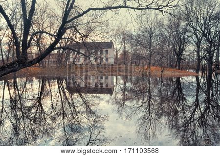 Spring landscape with small pond and old house on the background in the spring fog, mysterious spring landscape with old house. Spring landscape in the fog
