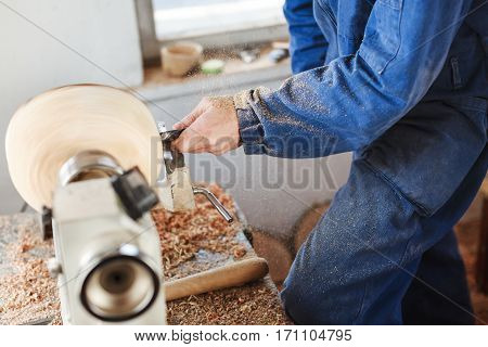 Man's hands in  blue jeans suit working with woodcarving machine and wood, shavings on table, close up.