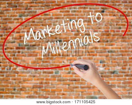 Woman Hand Writing Marketing To Millennials With Black Marker On Visual Screen