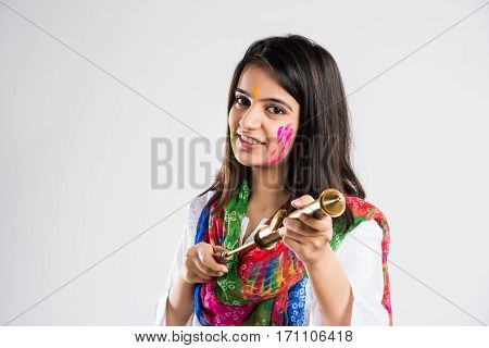 indian beautiful young female holding pichkari ready to spray colours on Holi festival, isolated over white background with copy space