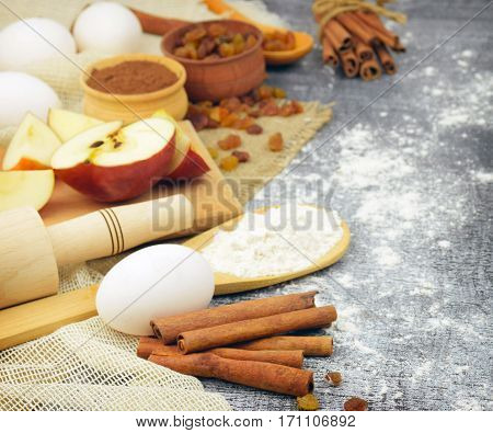 Ingredients for homemade pastries. Eggs, cinnamon, flour, apples, raisins, vanilla and cookware. Concept: home cooking. Traditions. Cosiness.