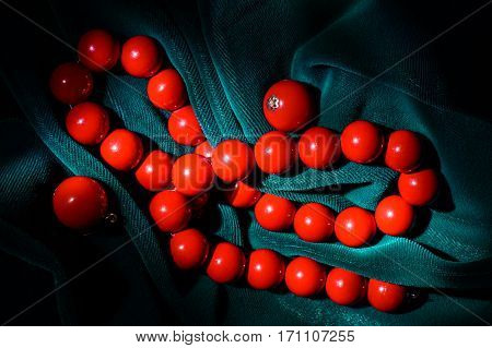 Red coral necklace and earrings at the dark green velvet background on the center of the frame.