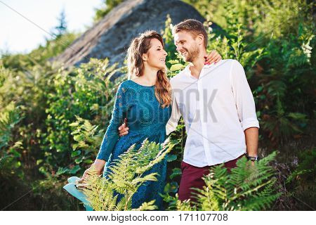 Nice couple standing together among fern and trees, outdoor, in the countryside. Beloved looking at each other, embracing each other by one hand and smiling. Woman wearing blue dress and has pink manicure and man wearing white shirt, claret trousers.