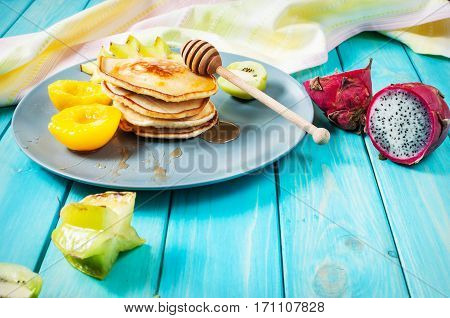 Pancakes with fruits on blue wood plate.
