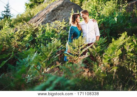 Nice couple standing together among fern and trees, outdoor, in the countryside. Beloved are looking at each other and embracing each other by one hand. Woman wearing blue dress and has pink manicure and man wearing white shirt, claret trousers. Profile