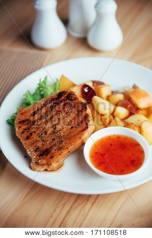 Steak with crispy golden fries and tomato spicy sauce.