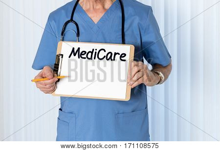 Senior male caucasian doctor with stethoscope in medical scrubs and holding clipboard for Medicare message with pencil for emphasis