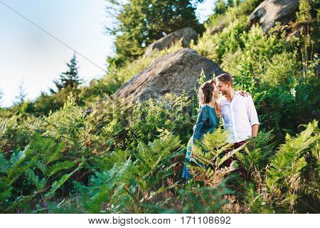 Nice couple standing together among fern and trees, outdoor, in the countryside. Beloved looking at each other, embracing each other by one hand and smiling. Very close to each other. Woman wearing blue dress and has pink manicure and man wearing white sh