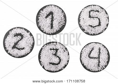 Numbers by salt on round stone board.