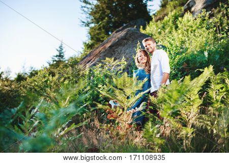 Nice couple standing together among fern and trees, outdoor, in the countryside. Beloved looking at camera, embracing each other by one hand and smiling. Woman wearing blue dress and man wearing white shirt, claret trousers.