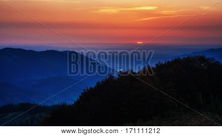 Red sunset in the mountains landscape with sunny beams. Carpathian, Ukraine, Europe. Instagram toning effect