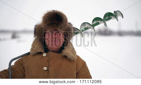 fisherman holding a borer for winter fishing and looking into the camera