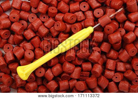 Red pre-drilled halibut pellets for carp fishing and yellow stinger needle background