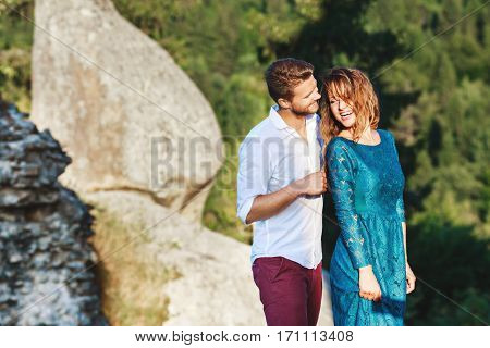Nice couple standing together near rock, outdoor, in the countryside. Girl looking aside and smiling and man looking at her. Woman wearing blue dress and man wearing white shirt and claret trousers