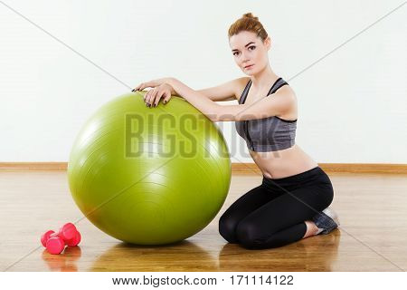 Young girl with light brown hair wearing black snickers, leggings and dark short top sitting with fitball and pink dumbbells at gym, fitness, white wall and wooden floor.