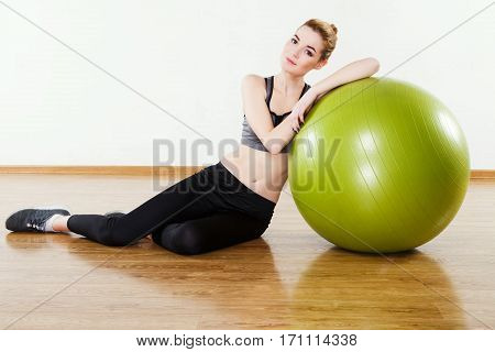 Cute girl with light brown hair wearing black snickers, leggings and dark short top sitting with fitball at gym, fitness, white wall and wooden floor, copy space.