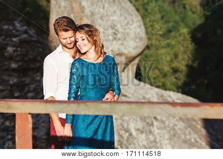 Nice couple standing together near rock and wooden bridge, outdoor, in the countryside. Girl has closed eyes, head turned aside and smiling and man holding her hand and embracing her with closed eyes and smiling too. Woman wearing blue dress and man weari