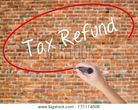 Woman Hand Writing Tax Refund With Black Marker On Visual Screen