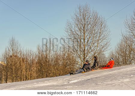 Belarus, Minsk - 07/02/2017: On the slope of the mountain snow three boys riding on sleds