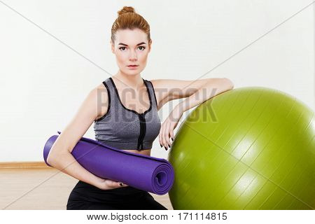 Beautiful girl with light brown hair wearing black leggings and dark short top sitting with fitball at gym, fitness, holding purple gym mat, copy space.