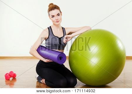 Gorgeous young girl with light brown hair wearing black snickers, leggings and dark short top sitting with fitball and pink dumbbells at gym, fitness, holding gym mat.