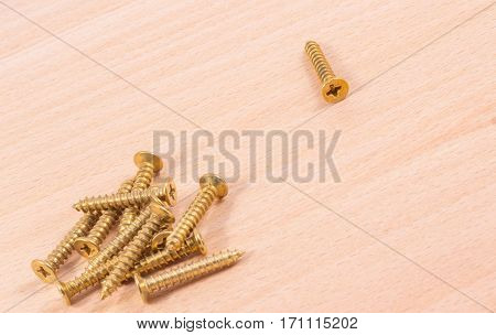 gold-colored screws on a wooden background tools for mounting threaded which are screwed into the holes
