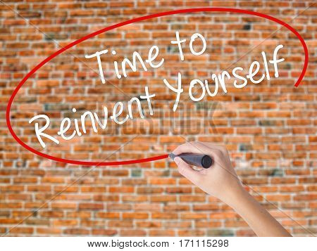 Woman Hand Writing Time To Reinvent Yourself With Black Marker On Visual Screen