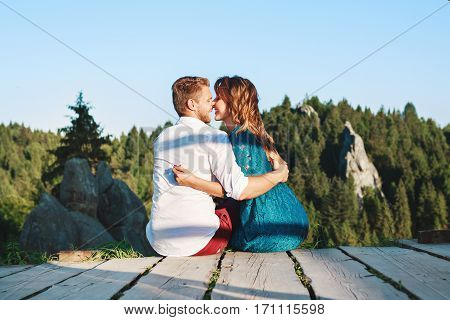 Cute couple sitting on a wooden path near rocks. Very close to each other. Their noses touching each other, man and woman have closed eyes and smiling. Nice beloved embracing each other by one hand. Woman wearing blue dress and man wearing white shirt and