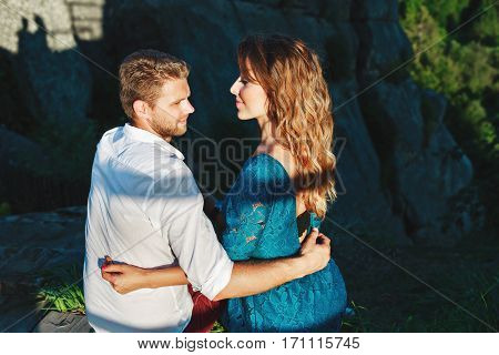 Cute couple sitting near rocks in shadow. Man looking aside and woman looking at him. Nice beloved embracing each other by one hand. Woman wearing blue dress and man wearing white shirt and claret trousers. Profile