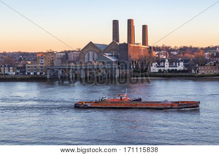 Barge on the Thames at Greenwich. Evening shot in winter with lovely light and shows a barge pulling an aggregate carrier up the River Thames.