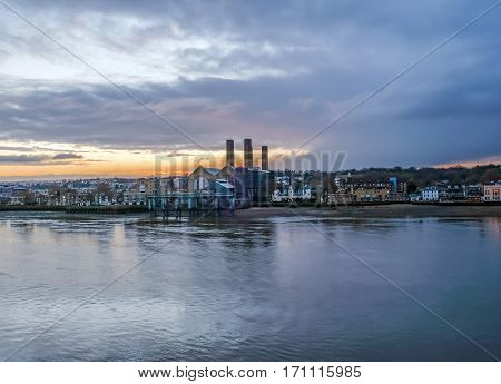 Greenwich at dawn. Early morning shot of the Power station at Greenwich and the Trinity Hospital with a beautiful sunrise sky.