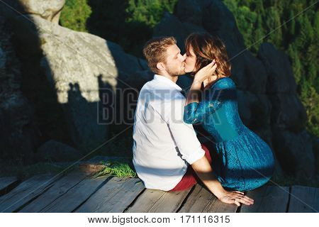 Cute couple sitting on a wooden path near rocks. Kissing beloved. Girl holding her hair by one hand. Woman wearing blue dress and man wearing white shirt and claret trousers. Profile