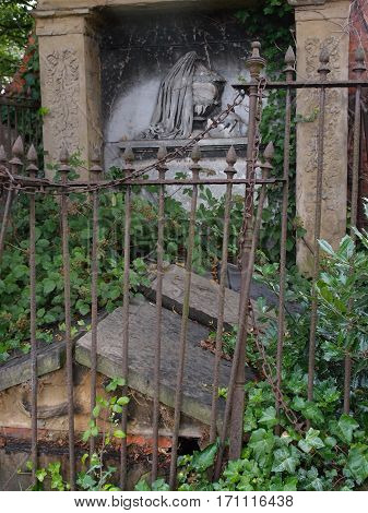 An old European tomb with an iron fence around it ornate stone carvings and covered in ivy has weathered the test of time but not without heavy damage.