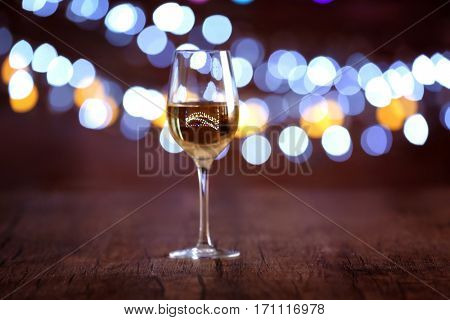 Glass of wine on wooden table and bokeh background