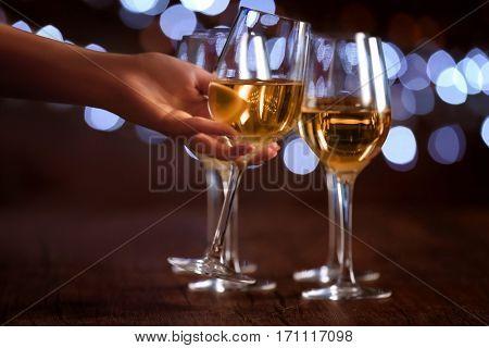 Female hand taking wine glass on bokeh background