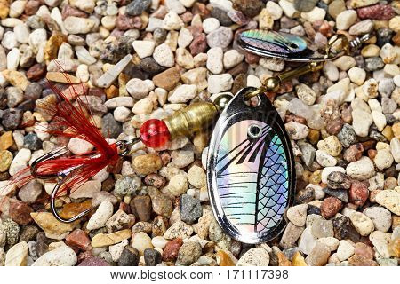 Metal fishing bait with the hologram decor on the stony ground