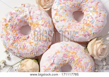 Delicious doughnuts and beautiful flowers, closeup