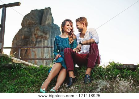 Nice couple sitting on grass near rock and wooden bridge, outdoor. Beloved looking at each other and smiling. Woman wearing blue dress and light blue shoes and man wearing white shirt, black shoes and claret trousers