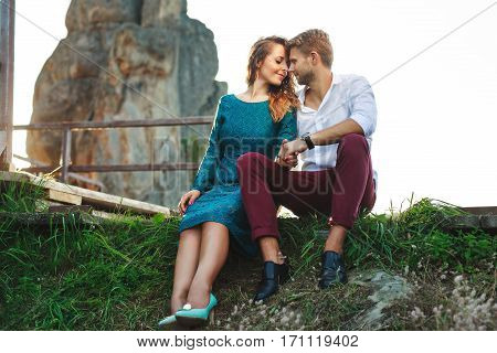 Nice couple sitting on grass near rock and wooden bridge, outdoor. Beloved touching each other with nose, have closed eyes and smiling. They holding hands of each other. Woman wearing blue dress and light blue shoes and man wearing white shirt, black shoe