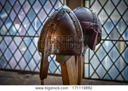 Steel knight helmet with hints of the sword impact on the window background