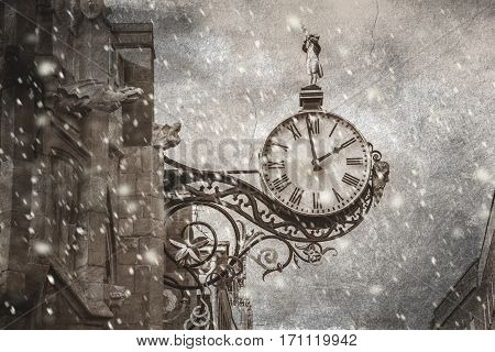 An old vintage clock fixed to wall in snowing time