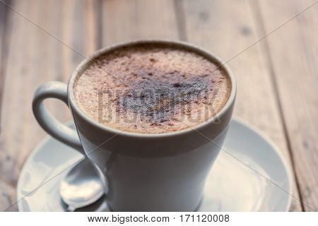 Cup of cappuccino with sprinkles over wooden table.