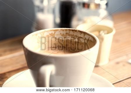 A half of cup of cappuccino over wooden table.