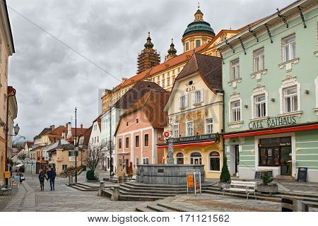 MELK/ AUSTRIA - FEBRUARY 23. Medieval buildings around the square Rathausplatz in the town of Melk with Benedictine abbey in the background on a cloudy day on February 23, 2016. Lower Austria.