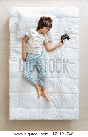 Wanna try everything. Charming serene young boy falling asleep in his bed and imagining himself playing computer games poster