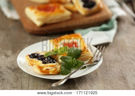Plate with sweet bilberry pastries on wooden background