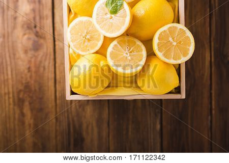 Lemons in a wooden box on a wooden table. Lemons on a wooden background. Lemons. Fruits. Lemon halves. Mint. Healthy food concept. Copyspace