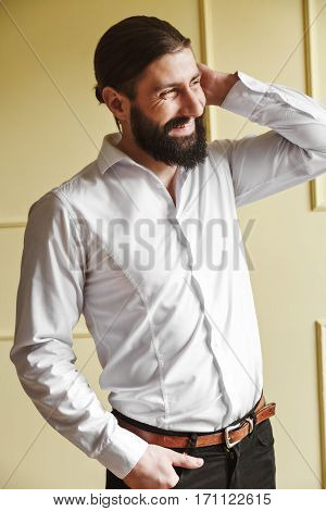 Man scratching his neck. Bridegroom looking aside and smiling. Man in white shirt with beard and moustache. Profile. Indoor, studio